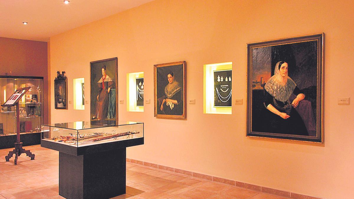 Sala femenina del Museu de Lluc con retratos y otros objetos.