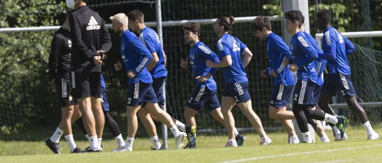 Ziganda, de espaldas, con los jugadores del Oviedo corriendo durante un entrenamiento.  
