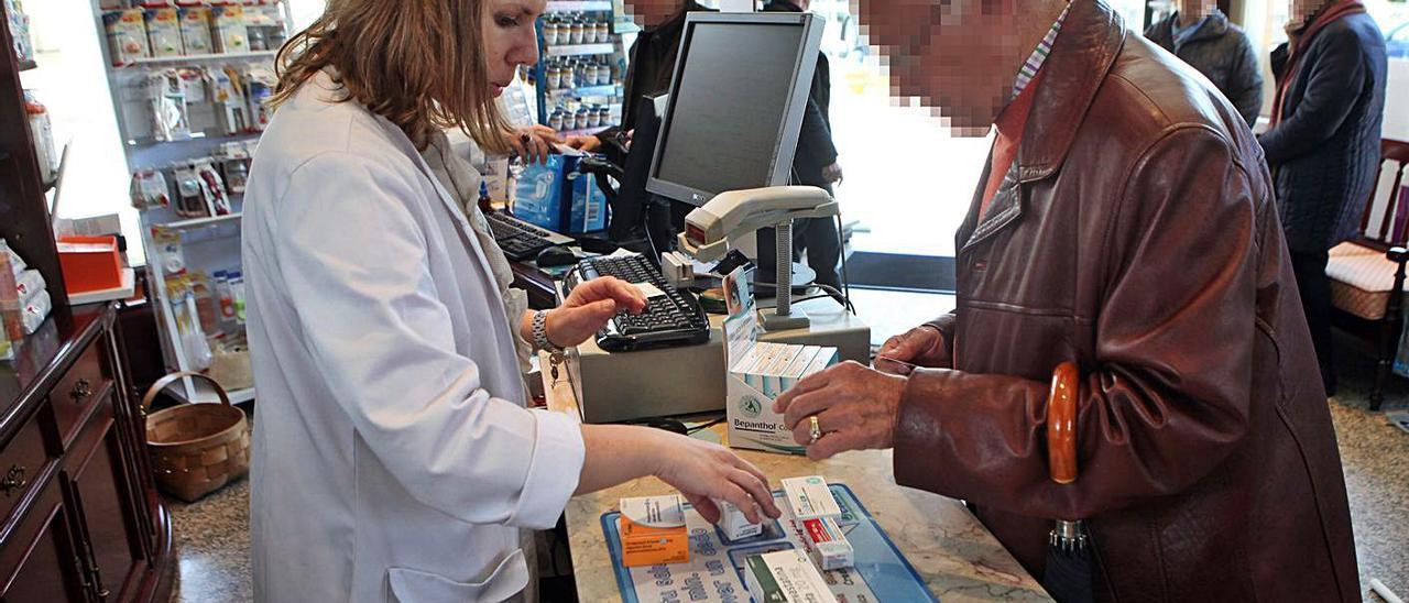 Un hombre compra medicinas en una farmacia de A Estrada.