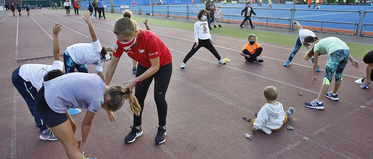La olímpica Rocío Ríos, en un entrenamiento en el Grupo Covadonga, con el equipo de hockey al fondo. A la izquierda, una de sus alumnas practica deporte en el centro gijonés. | |  Á. GONZÁLEZ