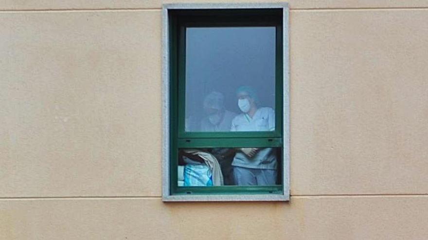 Dos trabajadores, ayer, en la ventana de la residencia DomusVi de Ribadumia. |   // IÑAKI ABELLA