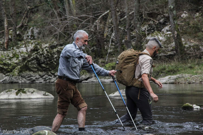 El geólogo Andrés Alonso, junto a Arcadio Noriega, cruzando el río Nalón en una investigación sobre arte rupestre.