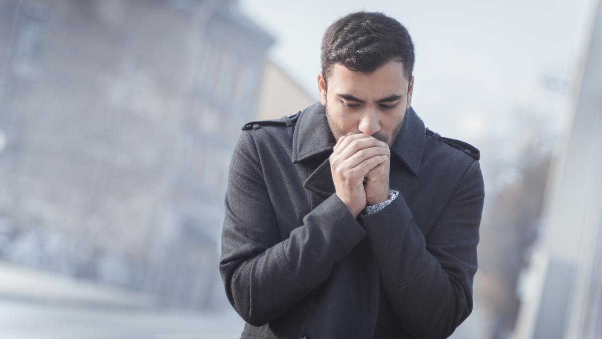 Un hombre trata de calentarse las manos