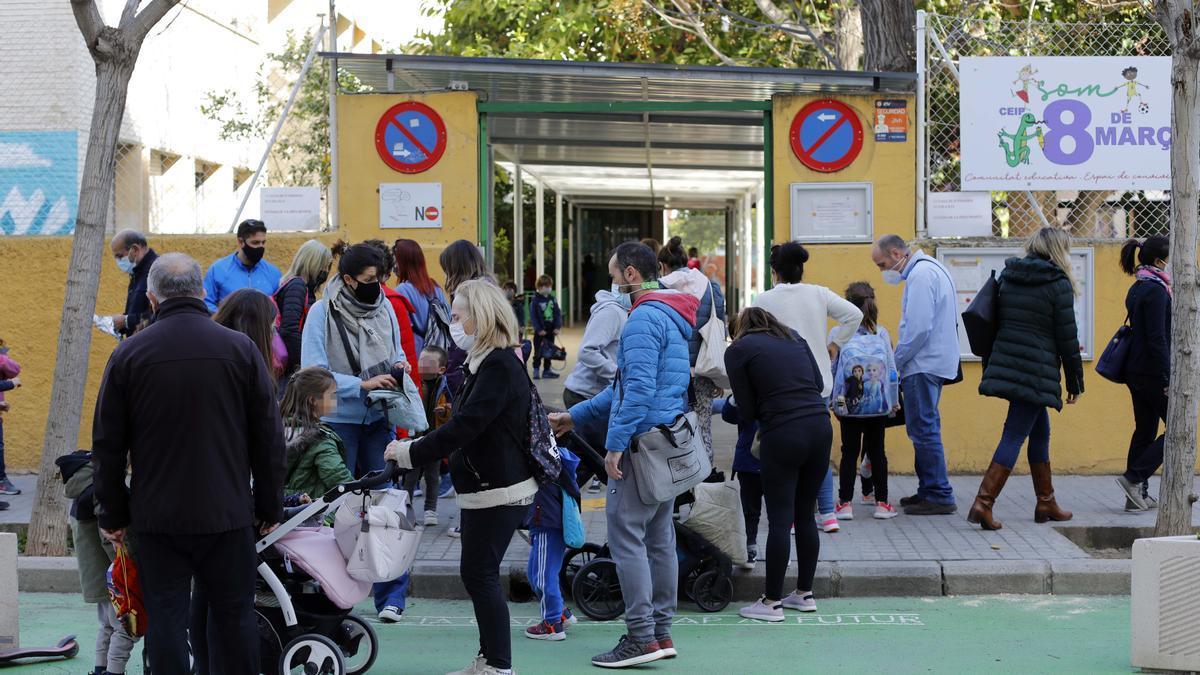 Padres, madres y escolares, a la salida de un colegio de València.