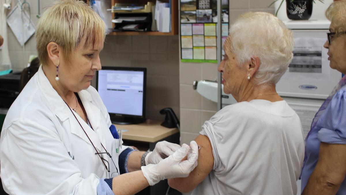 Una mujer se vacuna de la gripe en València