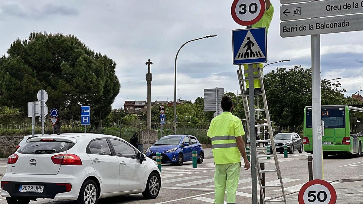 Dos operaris canviant un senyal de límit de velocitat, aquesta setmana a Manresa | AJ MANRESA
