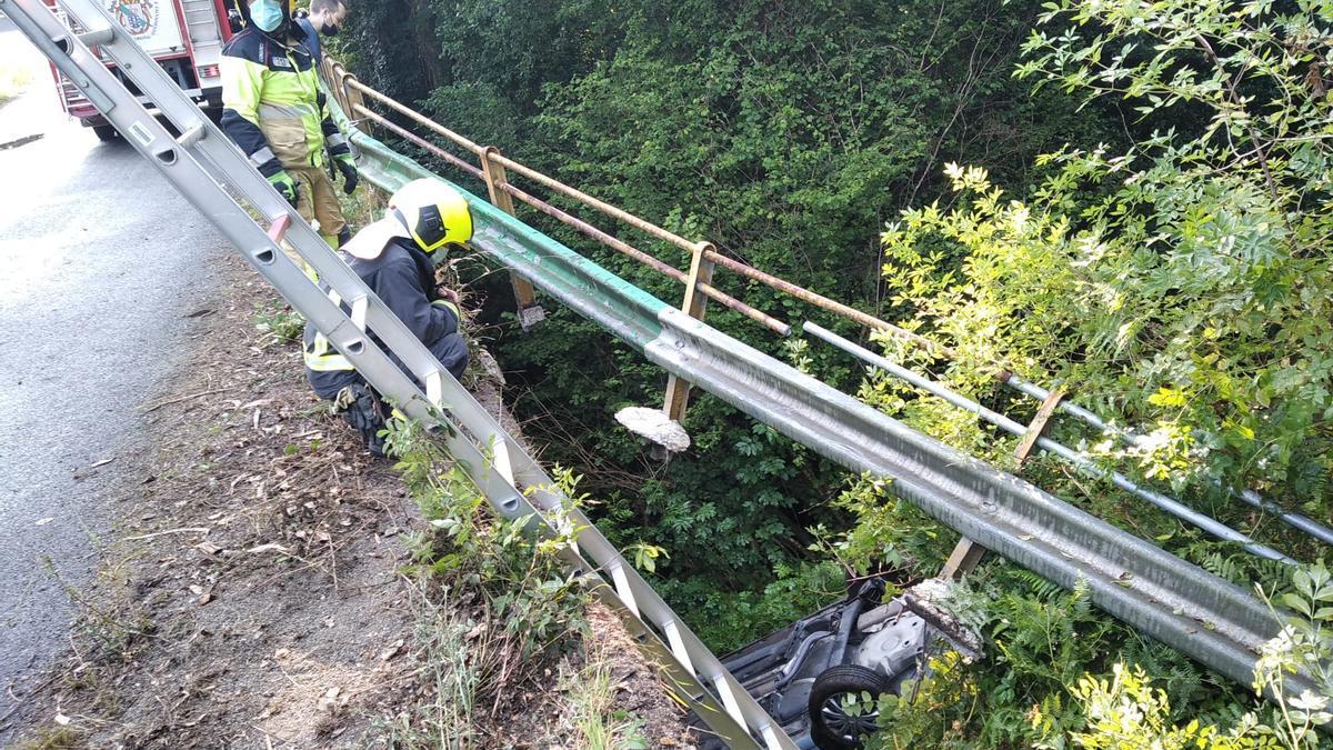 Efectivos del GES de Curtis intervienen para retirar el vehículo que se cayó hoy al río Mendo en un accidente en Oza-Cesuras.