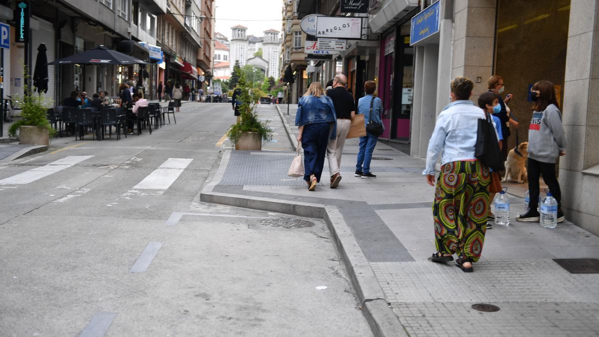 Ciudadanos con mascarilla y distancia social en una calle peatonal de A Coruña.