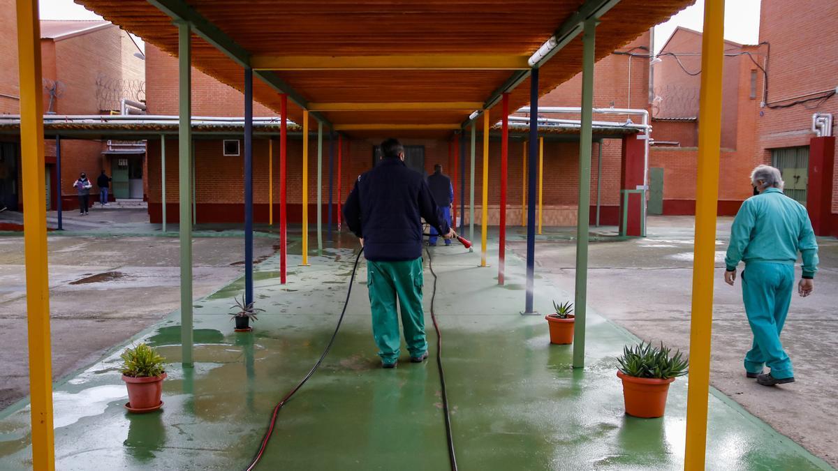 Trabajadores efectúan labores de limpieza en uno de los patios de la cárcel cacereña.