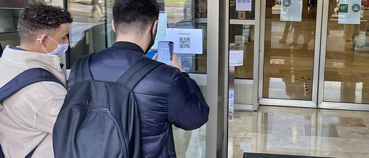 Dos alumnos utilizan la aplicación de registro en la entrada de la Politécnica de Mieres.   Vivas