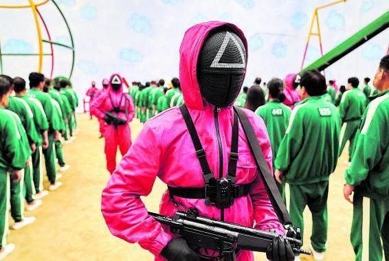 Concursantes en chándal verde, guardianes en mono rojo y sangre, en tres secuencias de la serie.