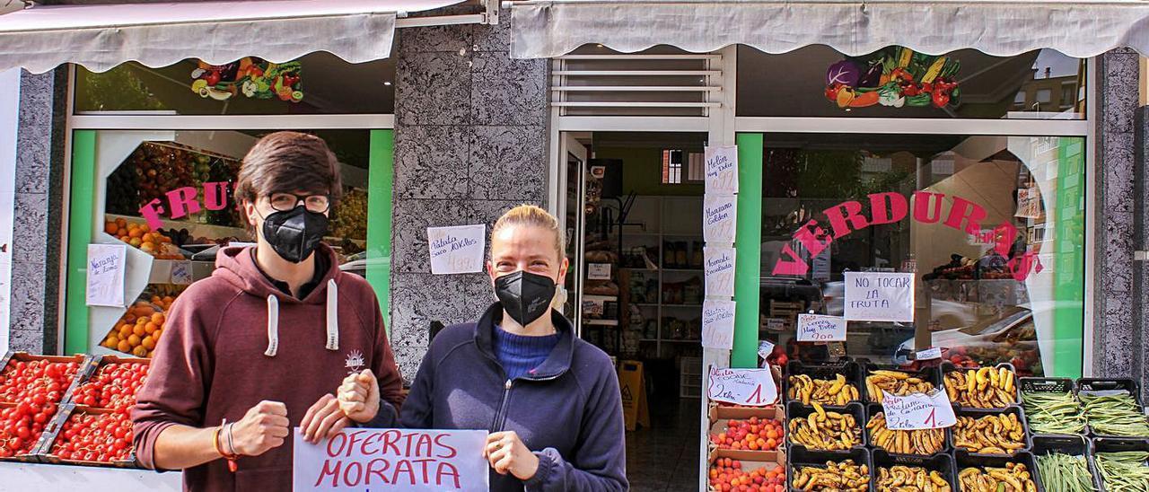 Por la izquierda, David Cadenas y Lorena Alonso, ayer, ante su frutería en Gijón.   Ulises Arce