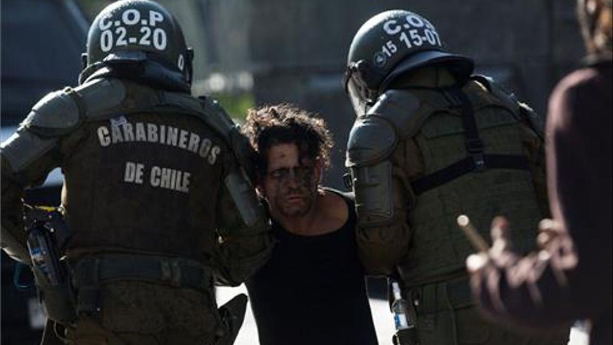 Carabineros detienen hoy a un manifestante durante una protesta junto al Palacio de La Moneda.