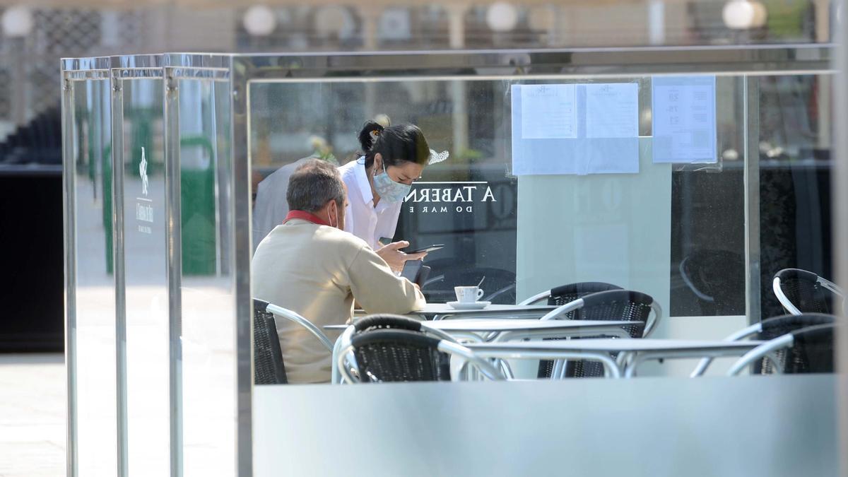 Un cliente en una terraza de O Grove con mamparas entre mesas.