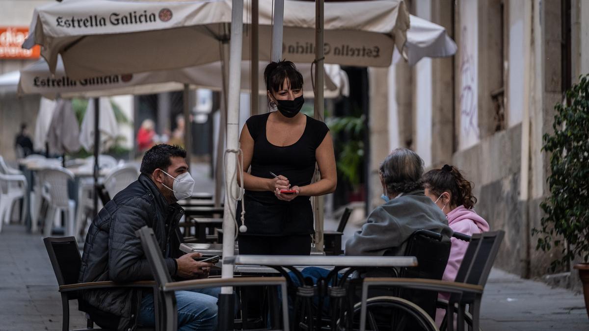 Una camarera atiende en terraza a unos clientes.