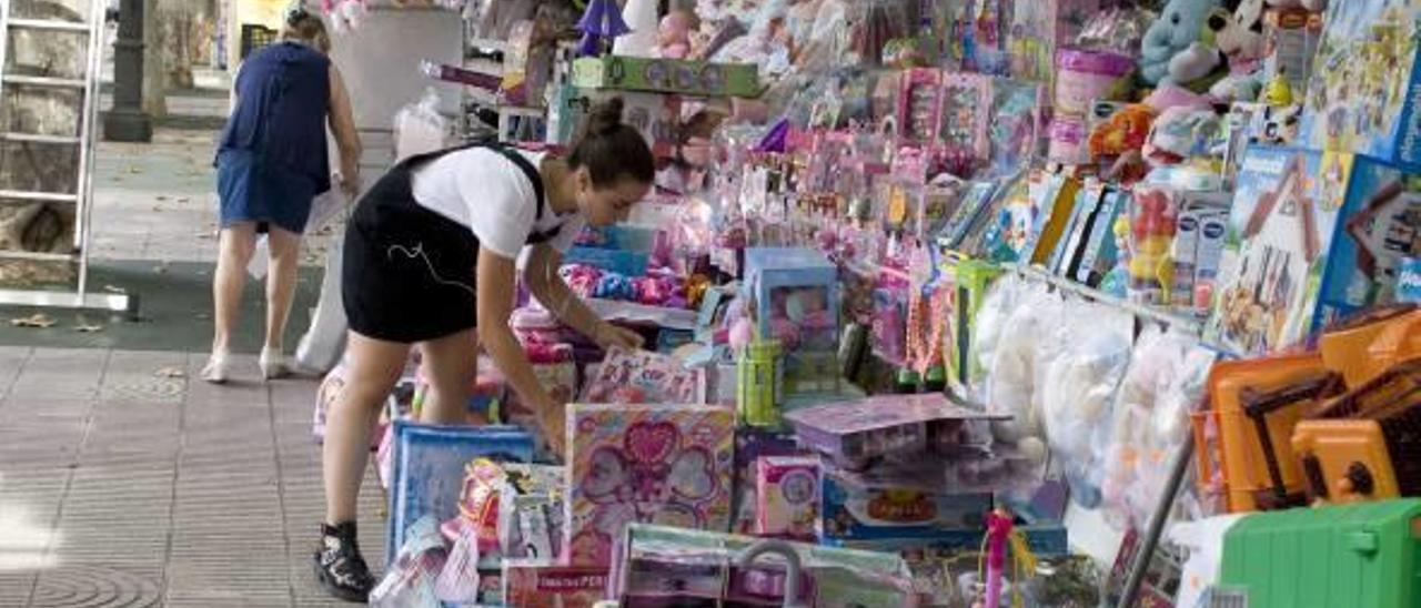 Tareas de montaje de un puesto de venta de juguetes en la última Fira d'Agost.
