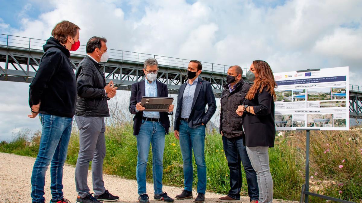 El conseller de Política Territorial, Arcadi España, junto al alcalde, Arturo Poquet, y los responsables de FGV, observando en una tablet el aspecto del futuro puente