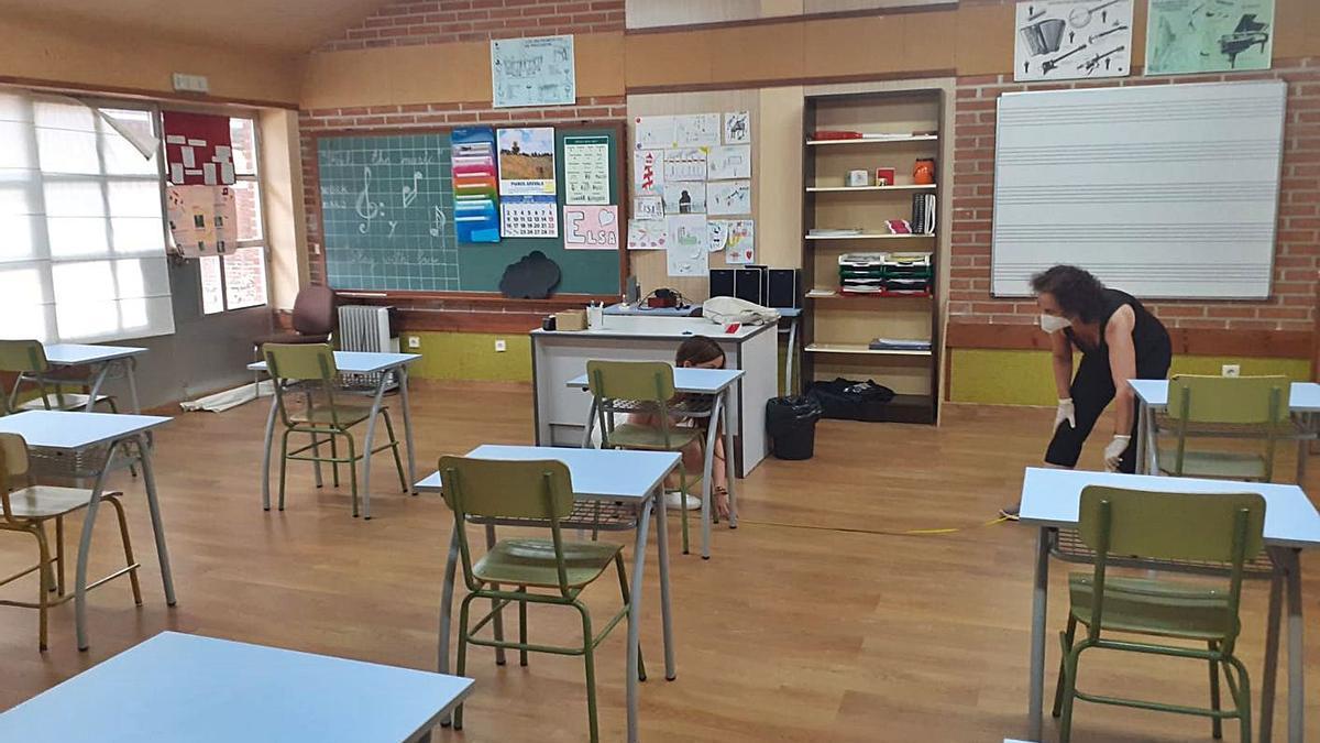 La directora de la escuela y personal docente preparando un aula para garantizar el cumplimiento de la distancia de seguridad. | C.G.R.