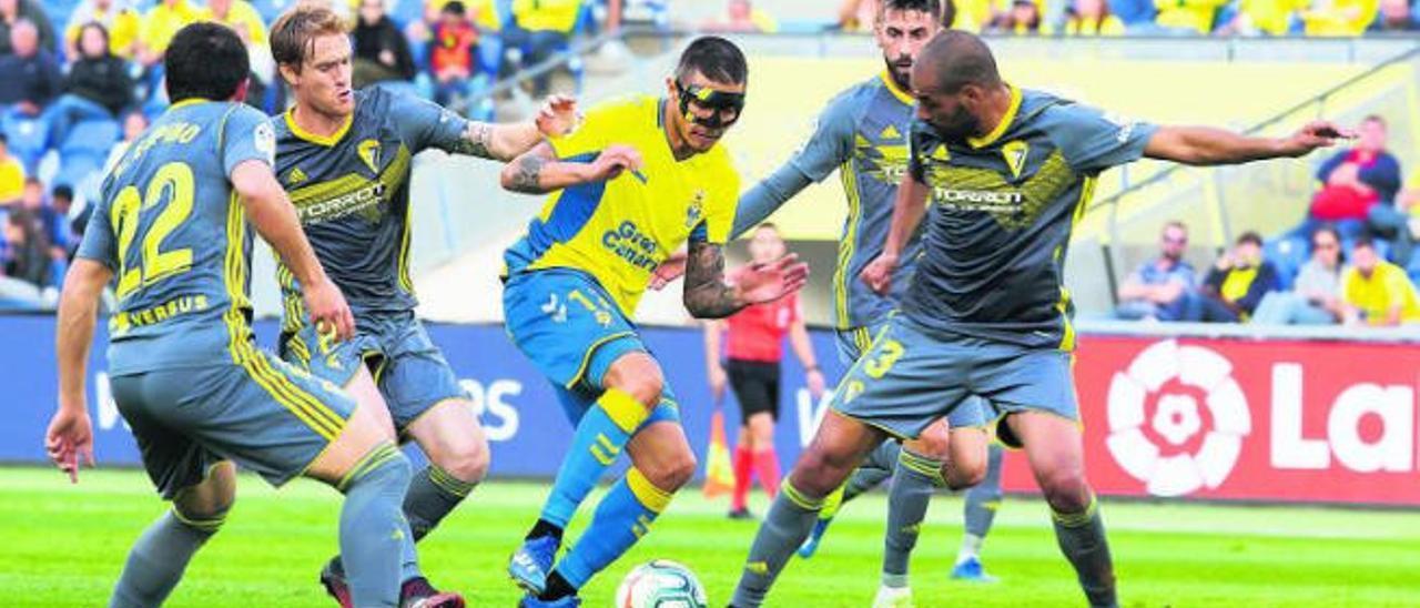 Juanjo Narvaéz, delantero de la UD Las Palmas, rodeado por cuatro futbolistas del Cádiz, ayer en el Estadio de Gran Canaria.