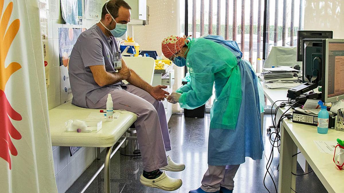 Una sanitaria realiza una prueba a otro compañero, en el hospital de Dénia en una foto de archivo.   | LEVANTE-EMV