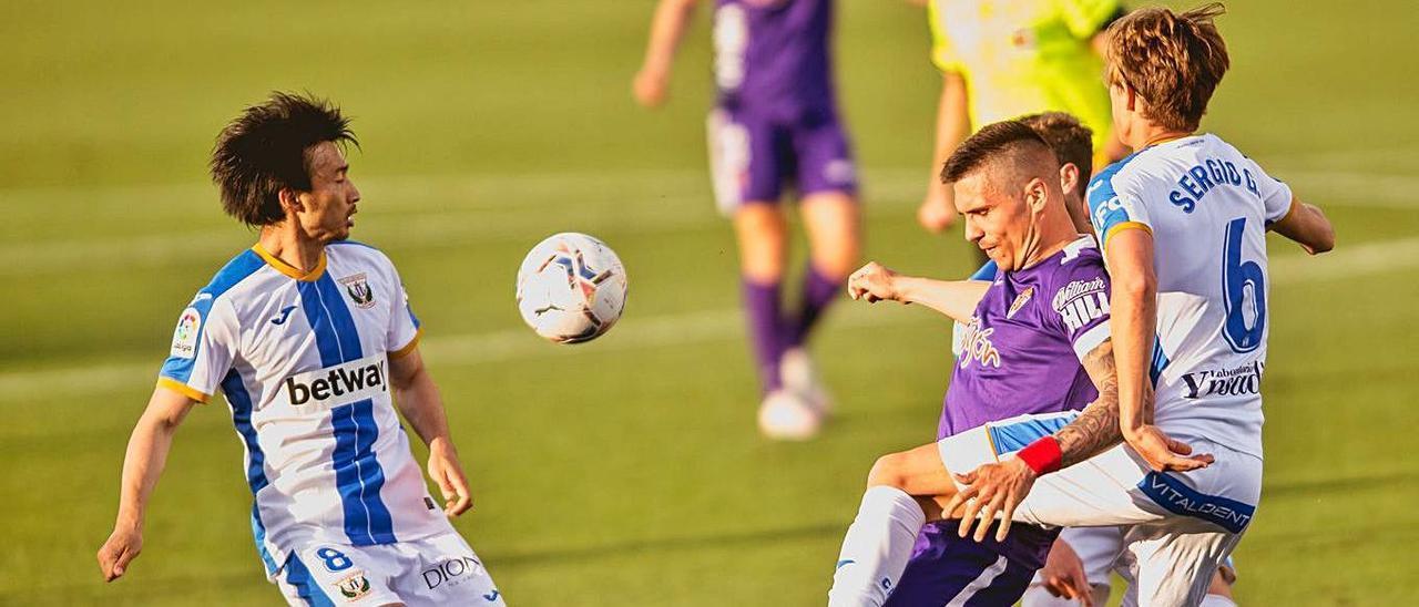 Djuka intenta controlar un balón presionado por tres contrarios.