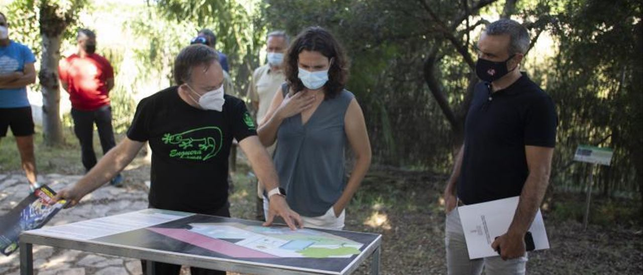 Fermín Poquet muestra a Paula Tuzón y Diego Marín uno de los mapas de la zona.   PERALES IBORRA