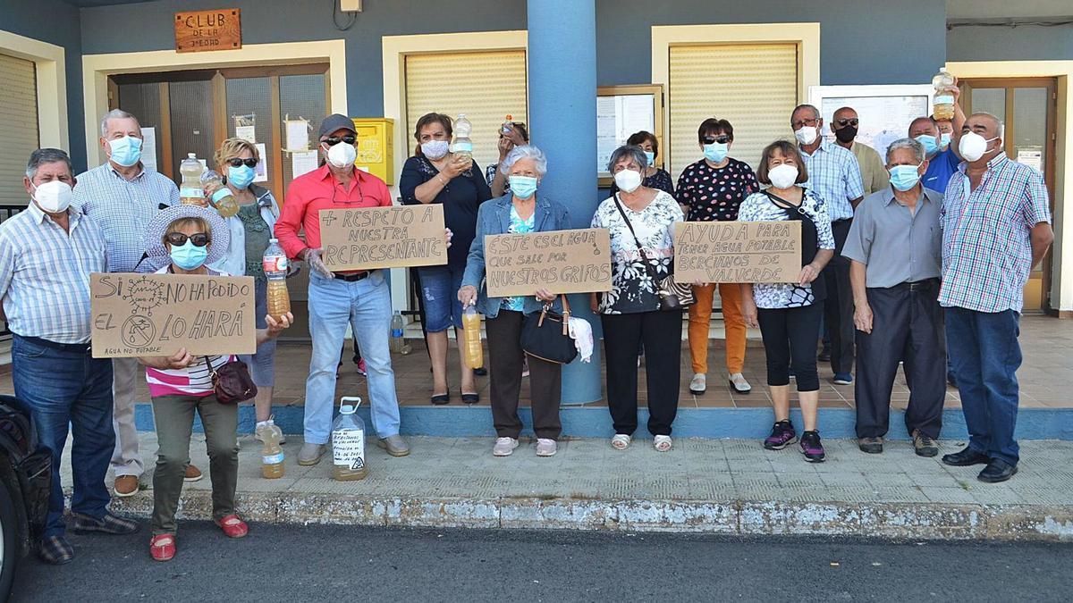 Varios vecinos de Bercianos, con carteles reivindicativos y agua embotellada esperando la llegada del alcalde de Pueblica al pleno. | E. P.