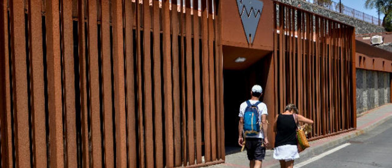 Dos turistas delante del Centro de Interpretación de Risco Caído.