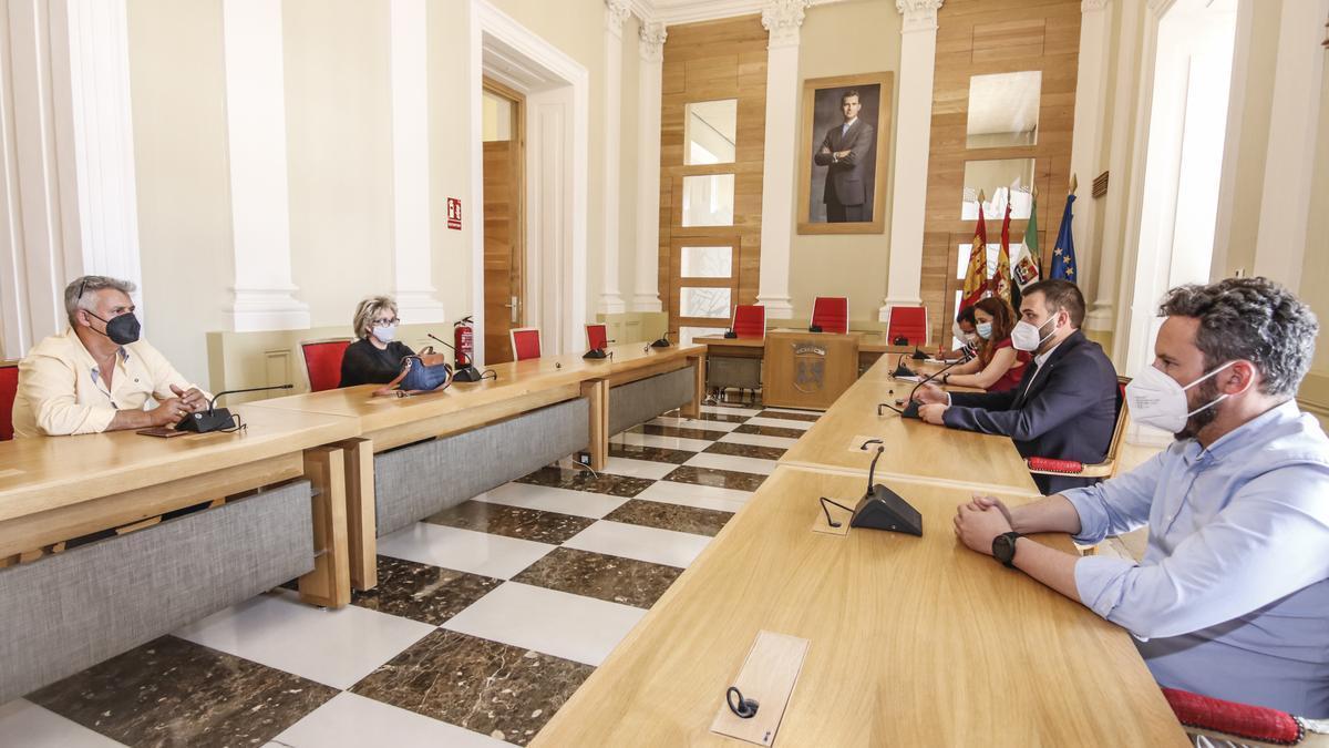 Feriantes y corporación municipal durante la reunión que se celebró este miércoles en el salón de plenos del ayuntamiento de Cáceres.