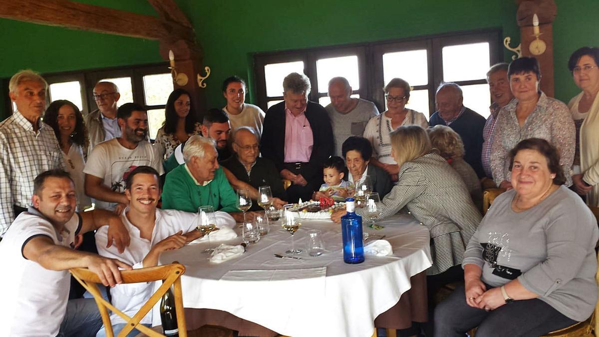 Elvira López, en el centro de la imagen, ante su tarta de cumpleaños, acompañada por sus familiares. | Reproducción de D. Á.