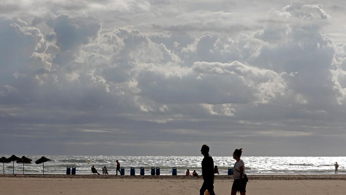 Varias personas hoy en la playa de la Malvarrosa de Valencia, donde ondea la bandera roja y en el que predomina las nubes con posibilidad de chubascos aislados y un bajada general de temperaturas.