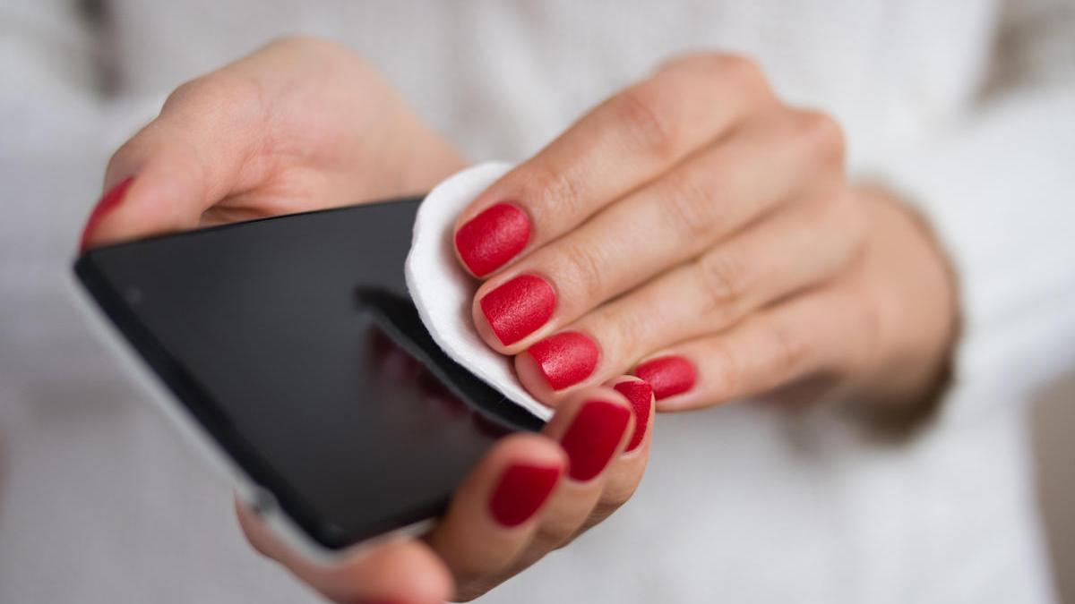 Una mujer limpia la pantalla de un teléfono móvil.