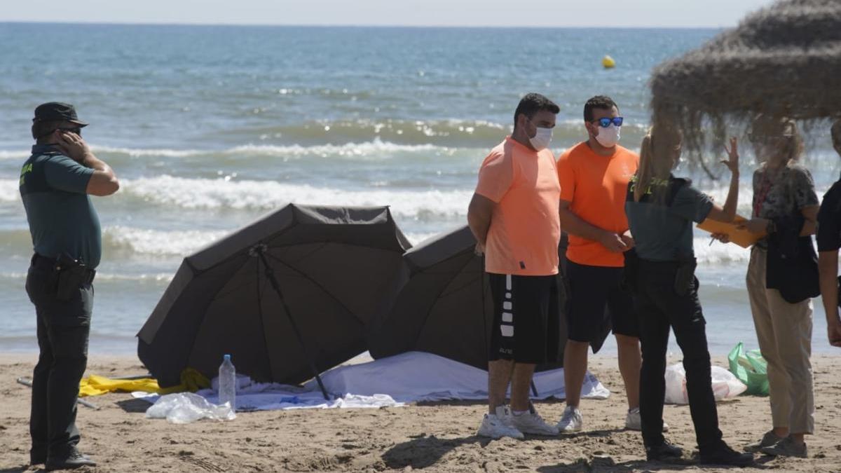 El cadáver de la mujer, cubierto con una sábana y custodiado por la Guardia Civil en la orilla de la playa.