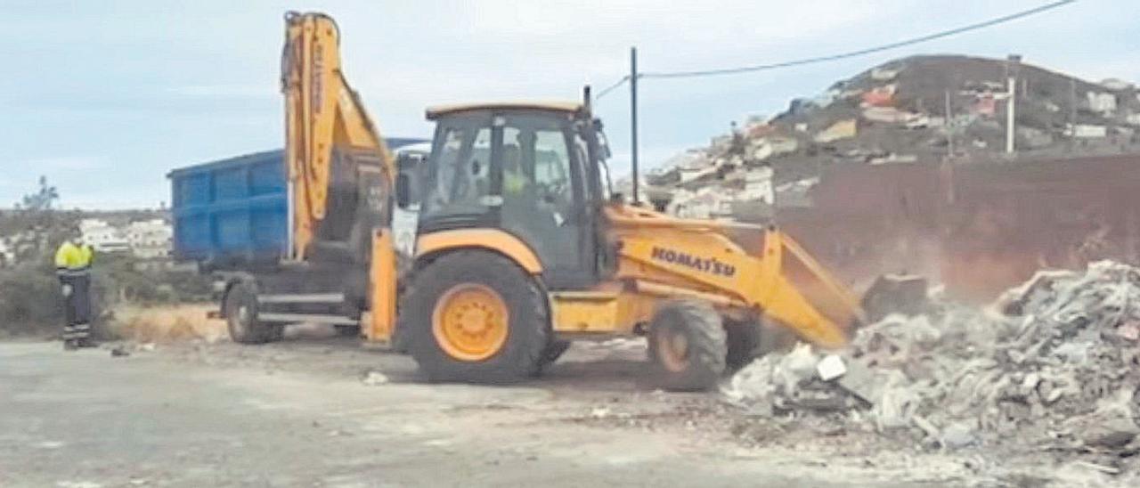 Un tractor recoge los escombros, para verterlos en un camión.