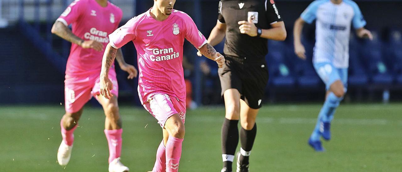 El extremo diestro de la UD Rober avanza con el balón, ante la presencia del árbitro Ais Reig, y el delantero Sergio Ezequiel Araujo.
