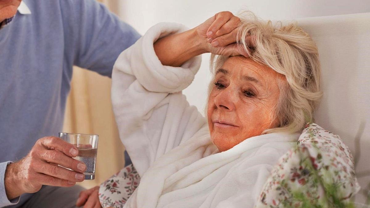 Una mujer que padece de fiebre y dolor de cabeza, encamada.