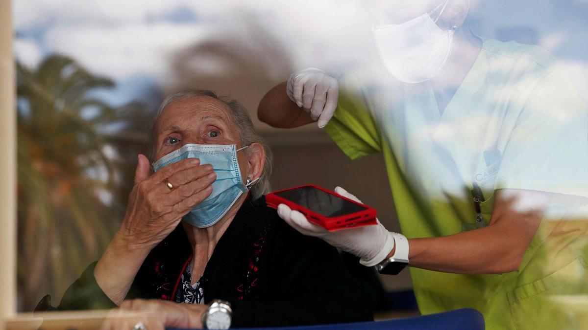 Una mujer se despide con un beso tras del cristal de una residencia