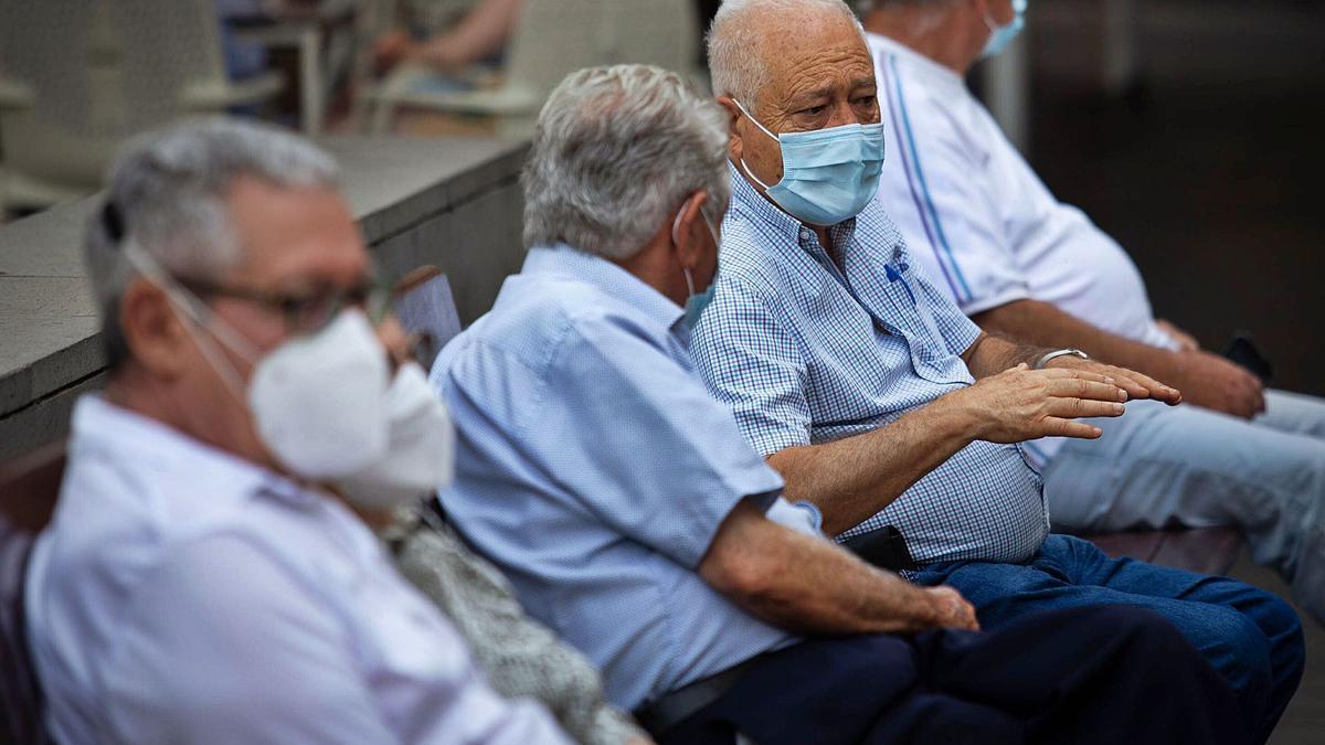 Varios ancianos charlan sentados en un banco de Santa Cruz de Tenerife.