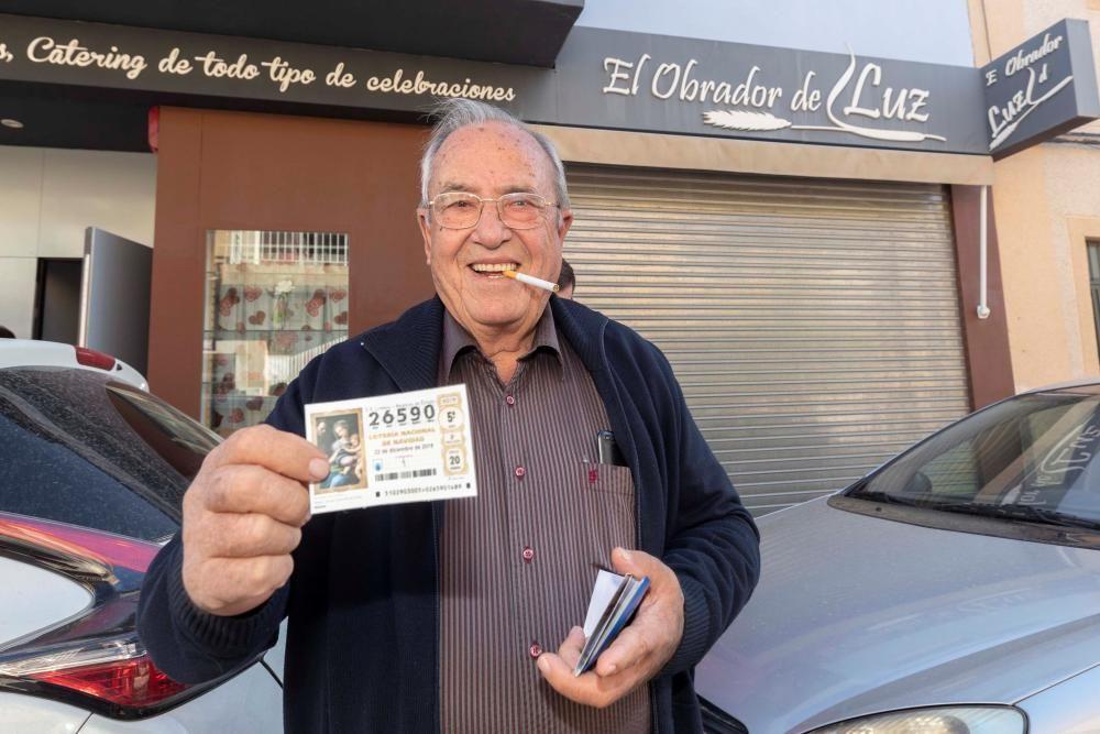 El agraciado con el Gordo de la lotería de navidad Santiago Palazón muestra el décimo premiado junto al obrador donde lo compró en Murcia.
