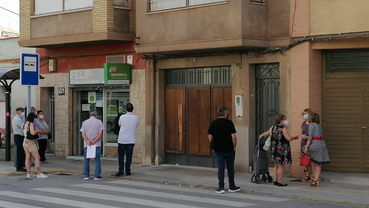 Clientes de una compañía eléctrica, haciendo cola en el exterior de un punto de atención al cliente de Almassora.