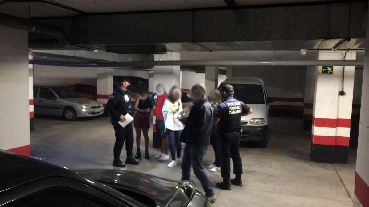 Momento en el que la Policía Local de Las Palmas de Gran Canaria desaloja un botellón en un garaje en San Cristóbal.