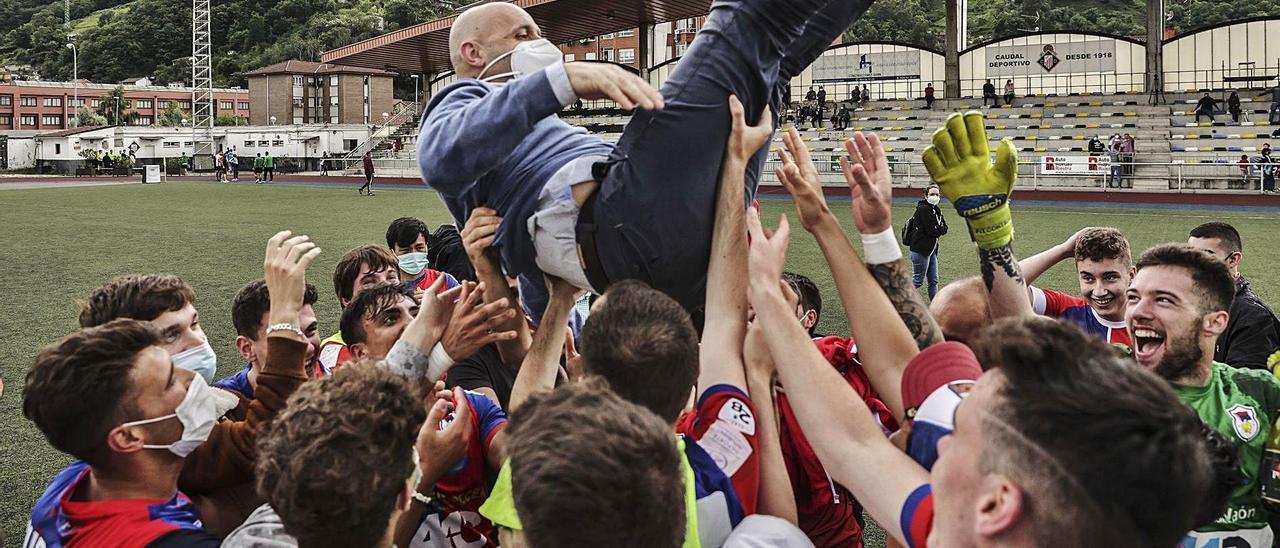 Ricardo Terente es manteado por sus lugadores tras lograr el ascenso ante el Nalón. |