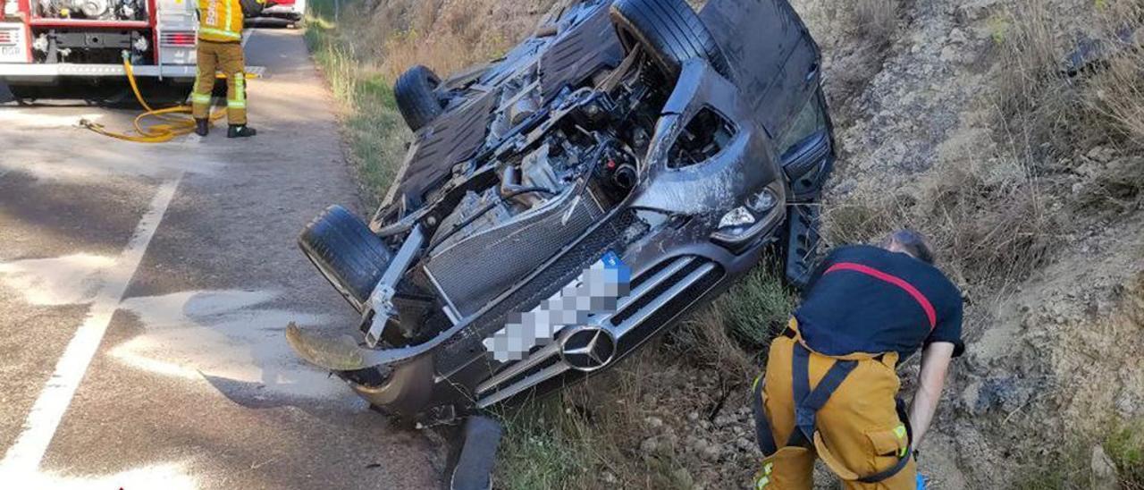 Tareas de rescate de la conductora atrapada tras volcar su vehículo en Alcoy este martes.