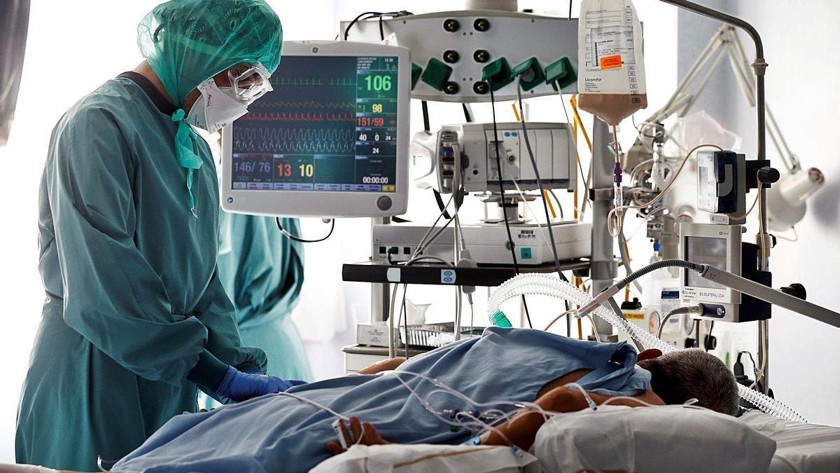 Paciente y enfermera en la Unidad de Cuidados Intensivos del Hospital General de Elche.