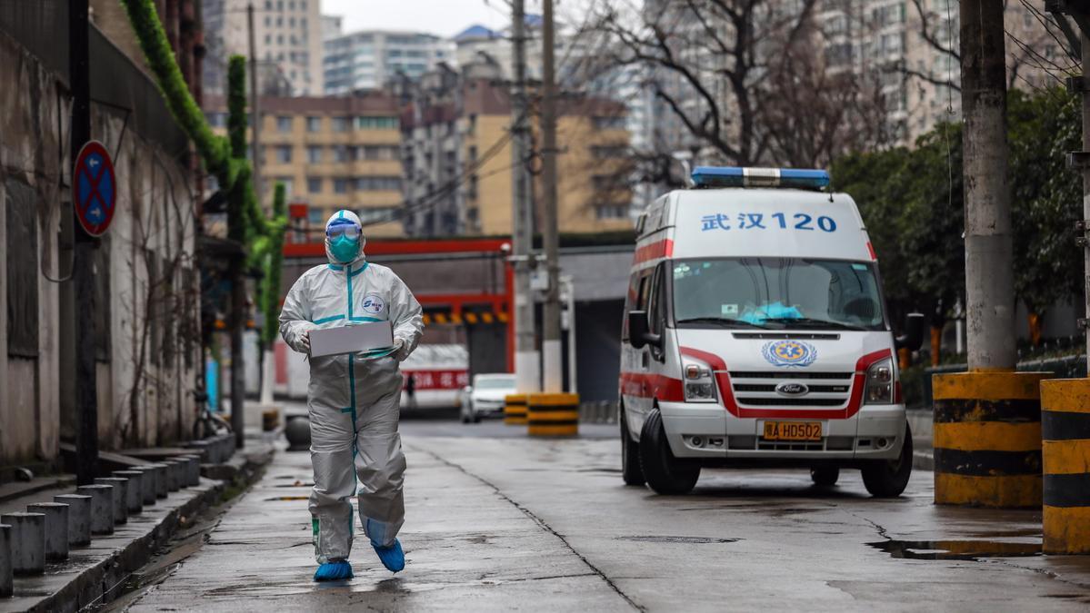 Un sanitario chino carga una caja con suministros médicos a finales de enero en los alrededores de un hospital de Wuhan