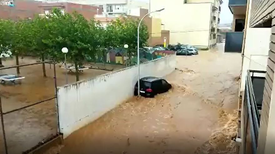 l'aigua baixant per un dels carrers d'Alcanar, on han caigut fortes pluges, causant diverses inundacions