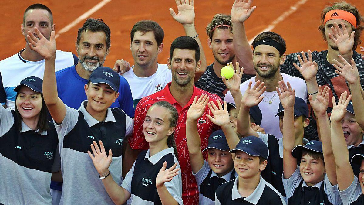Dimitrov a la izquierda de Djokovic y con cinta negra, posa con varios tenistas y recogepelotas.
