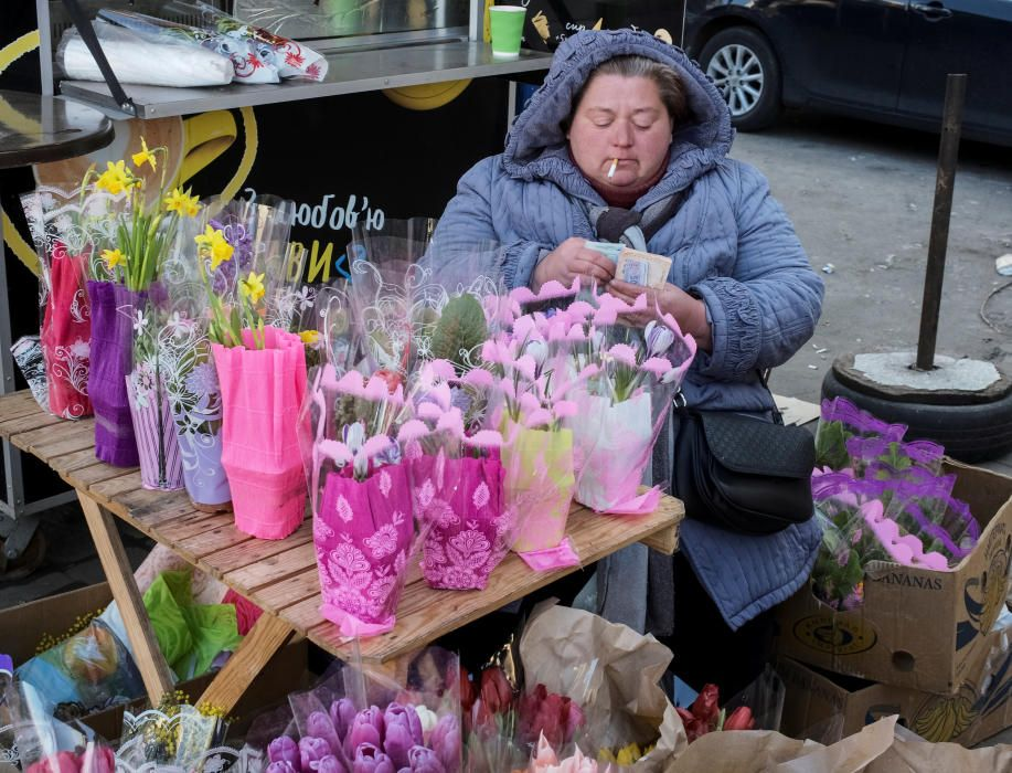 A woman counts her money as she sells flowers ...
