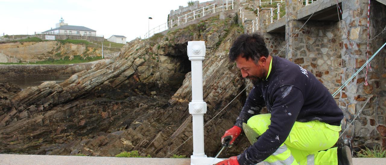 Un operario renovando la pintura de las barandillas del puerto de Tapia.