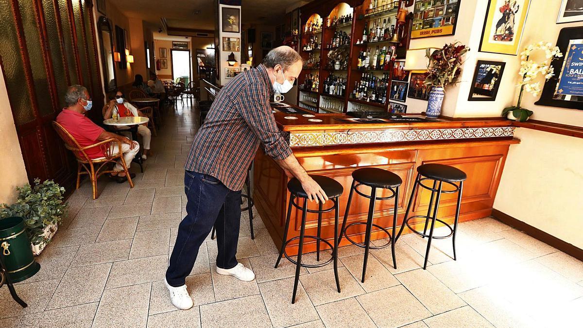 El propietario del Rag Time, en Zaragoza, coloca los taburetes junto a la barra en la última relajación de medidas en interiores para la hostelería. | JAIME GALINDO